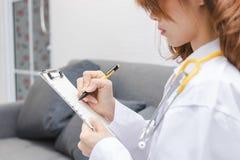 Молодые азиатские женские примечания сочинительства доктора на доске сзажимом для бумаги в офисе больницы стоковые фото
