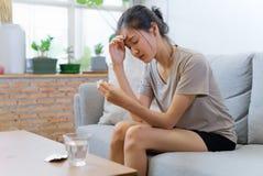 Молодые азиатские женщины на софе закрывая ее глаза страдают от головной боли и имеют некоторую лихорадку стоковое фото rf