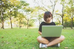 Молодые азиатские ноги ` s женщины на зеленой траве с открытой компьтер-книжкой Руки ` s девушки на клавиатуре Стоковые Фото
