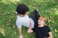 Молодые азиатские пары влюбленности ослабляют после тренировки в парке путем играть друг к другу с эмоцией влюбленности в теплом  Стоковое Фото