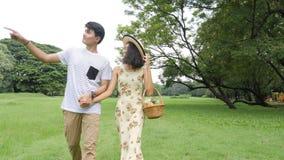 Молодые азиатские пары наслаждаясь весной днем в природе и идя на пикник со счастливой эмоцией акции видеоматериалы