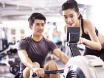 Молодые азиатские пары разрабатывая используя машину rowing Стоковое Фото