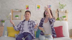 Молодые азиатские пары сидя на банкнотах софы улавливая бумажных видеоматериал