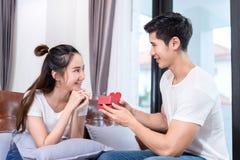Молодые азиатские пары совместно, сюрприз удерживания человека стоковые изображения rf