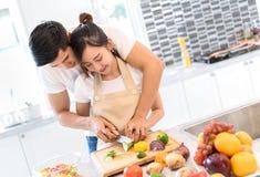 Молодые азиатские пары человека и женщины совместно режа овощи куска стоковое фото rf