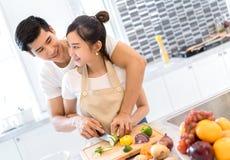 Молодые азиатские пары человека и женщины совместно режа овощи куска стоковые изображения