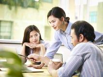 Молодые азиатские предприниматели обсуждая бизнес-план в офисе Стоковое Изображение RF