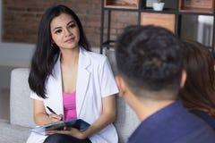 Молодые азиатские счастливые пары советуя с с доктором Стоковые Фотографии RF