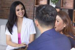 Молодые азиатские счастливые пары советуя с с доктором Стоковые Изображения