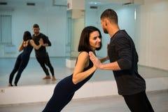 Молодые атлетические пары в темных костюмах практикуя йогу пар в студии с зеркалами Балансировать в парах стоковая фотография