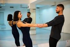 Молодые атлетические пары в темных костюмах практикуя йогу пар в студии с зеркалами Балансировать в парах стоковое изображение
