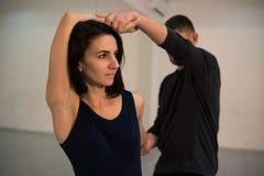 Молодые атлетические пары в темных костюмах практикуя йогу пар в студии с зеркалами Балансировать в парах стоковые изображения rf