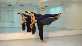 Молодые атлетические пары в темных костюмах практикуя acroyoga в студии с зеркалами Балансировать в парах видеоматериал