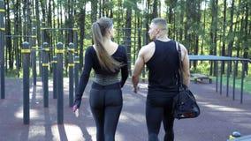 Молодые атлетические пары идя после тренировать outdoors видеоматериал
