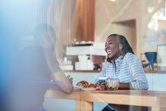 Молодые африканские пары lauging совместно пока сидящ в кафе Стоковые Изображения RF