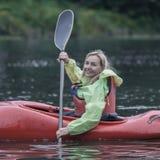 Молодые белокурые заплывы девушки на шлюпке спорт сплавляться на красивом ri Стоковое Фото