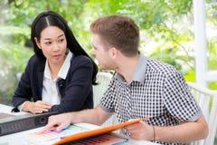 Молодые бизнесмены делая встречу и смотря документ для анализировать маркетинг работая на офисе Стоковые Изображения RF