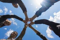 Молодые бизнесмены кладя их руки совместно, backgrou неба стоковое фото rf