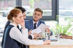 Молодые бизнесмены обсуждая проект в современном Стоковая Фотография