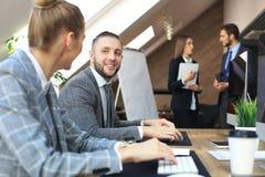 Молодые бизнесмены работая на их настольных компьютерах на современных размерах офиса стоковые фото