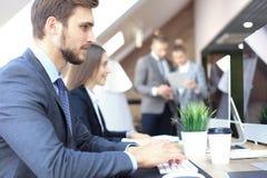 Молодые бизнесмены работая на их настольных компьютерах на современных размерах офиса стоковая фотография