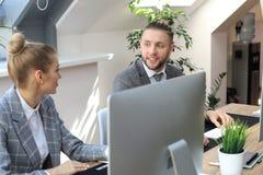 Молодые бизнесмены работая на их настольных компьютерах на современных размерах офиса стоковое фото rf