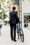 Молодые бизнесмены с велосипедом стоковое изображение