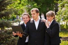 Молодые бизнесмены с компьтер-книжкой Стоковые Фотографии RF
