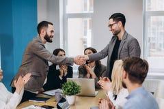 Молодые бизнесмены тряся руки в офисе Заканчивая успешная встреча стоковое изображение rf