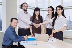 Молодые бизнесмены тряся руки в офисе Стоковое Изображение