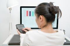 Молодые бизнес-леди работают с настольным компьютером калькулятора и компьютера и пишут на современной таблице работы Стоковое Фото