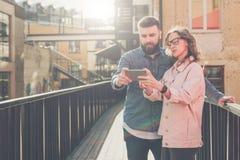 Молодые бородатые человек и женщина стоят снаружи и обсуждают чего они видят на экране smartphone Девушка показывает данные по па Стоковые Фото