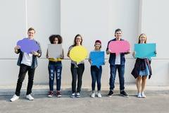 Молодые взрослые друзья задерживая плакат космоса экземпляра стоковое фото rf
