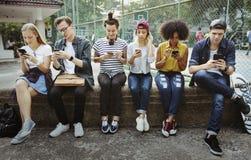 Молодые взрослые друзья используя cu молодости smartphones совместно outdoors стоковое фото rf