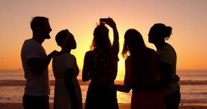 Молодые взрослые друзья принимая selfies на пляже на заход солнца 4k акции видеоматериалы