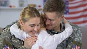 Молодые военные пары обнимая дочь, соединение семьи, счастье возвращения домой сток-видео