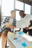 Молодые восторженные коллеги используя компьтер-книжку в офисе Стоковая Фотография RF