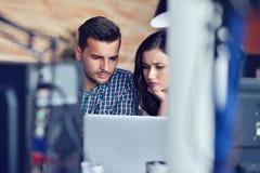 Молодые вскользь пары дела используя компьютер в офисе Coworking, творческий менеджер показывая новую startup идею Стоковое Изображение