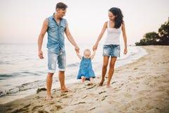 Молодые гетеросексуальные пары семьи Кавказские мама и папа учат идут малыш держа руки ребенка на песчаном пляже близко стоковые фотографии rf