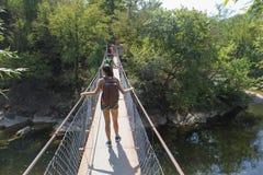 Молодые девушка и hikers путешественника идут через висячий мост перемещение карты dublin принципиальной схемы города автомобиля  Стоковые Изображения RF