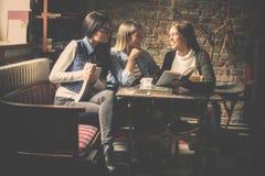 Молодые девушки студентов сидя в кафе и уча togeth Стоковое Изображение