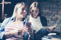Молодые девушки студентов уча и используя умный телефон Стоковые Фотографии RF