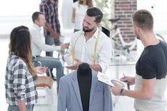 Молодые дизайнеры обсуждая мужской костюм стоковая фотография rf