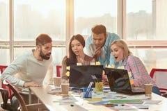 Молодые дизайнеры сети смотря компьтер-книжку и сотрясать Стоковое Изображение RF