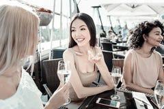 Молодые дружелюбные девушки сидя и говоря друг к другу Стоковое Фото