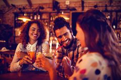 Молодые друзья взаимодействуя друг с другом имеющ пить стоковое изображение