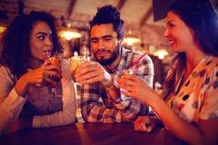 Молодые друзья взаимодействуя друг с другом имеющ пить стоковые изображения