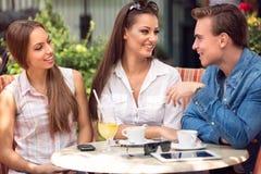 Молодые друзья встречая в кафе стоковые изображения