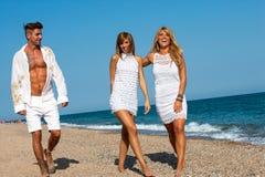 Молодые друзья гуляя вдоль солнечного пляжа. Стоковые Фотографии RF