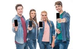 Молодые друзья держа smartphones Стоковое Изображение